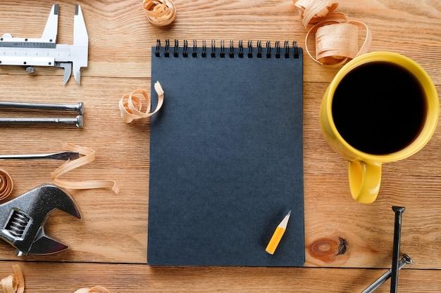 Gereedschap, kladblok en koffie op een houten tafel. bouwgereedschap op houten planken. bouw concept.