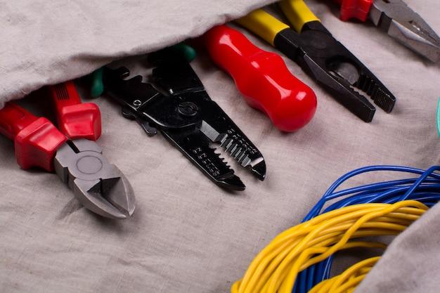 Gereedschap voor elektricien en bedrading op de stof