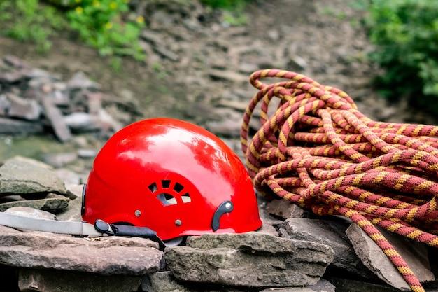 Gereedschap voor toegang tot touw: helm, touw, karabijnhaak. bergbeklimmersuitrusting op rotsen tegen een achtergrond van rotsen en groen