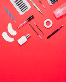 Gereedschap voor wimperverlenging op een rode achtergrond