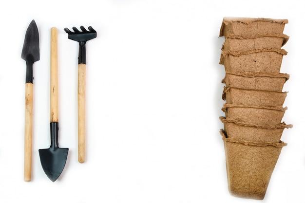 Gereedschap, zaden, turfpotten en geperste grond voor zaailingen. copyspace voor tekst, bovenaanzicht. voedsel verbouwen op de vensterbank. flatlay op witte houten ruimte
