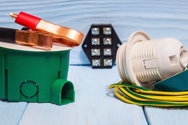 Gereedschappen en accessoires die worden gebruikt bij elektrische installatie of reparatie op blauwe houten planken