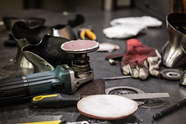 Gereedschappen en hardware op werkplaatstafel. werkplaats van een metaalmachinist die middeleeuwse pantserpakken produceert