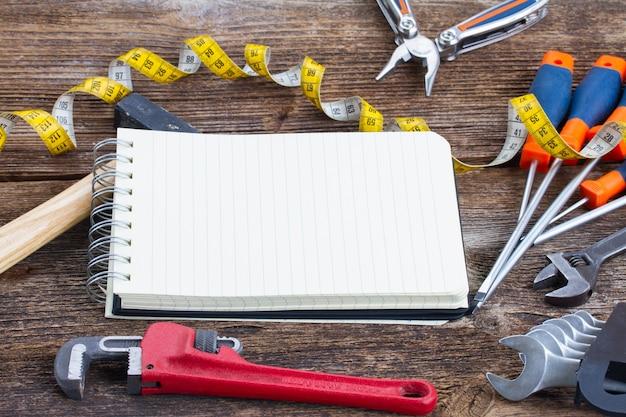 Gereedschapskit frame en leeg notitieboekje op houten parketplanken