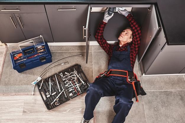 Gereedschapskoffer bovenaanzicht van senior klusjesman die wastafel repareert