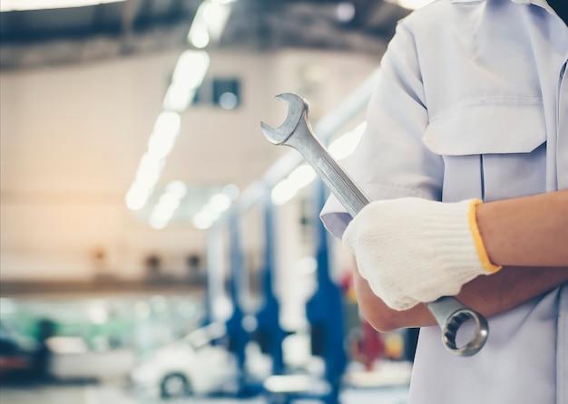 Gereedschapsleutel wordt vastgehouden door een monteur-reparateur met autoreparatieservice in het servicecentrum.