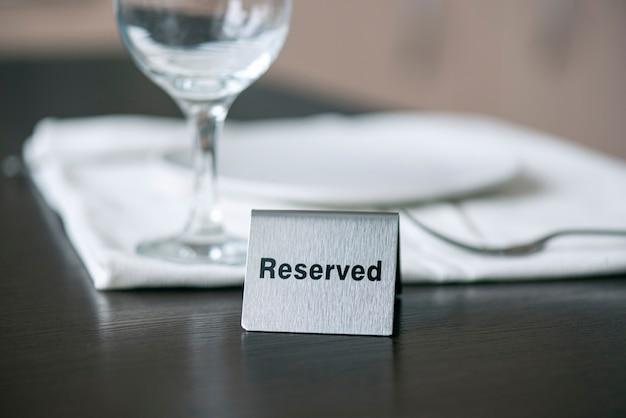 Gereserveerd ijzeren bord op houten tafel voor wit tafelkleed en wijnglas in een café of restaurant