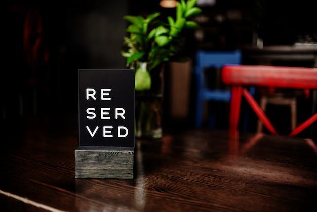 Gereserveerd teken op een tafel in restaurant. rode stoel en vaas. horizontale weergave van meerdere objecten.