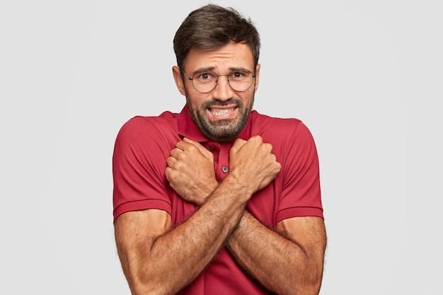 Gereserveerde stressvolle emotionele jongeman poseren tegen de witte muur