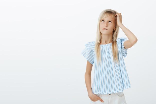 Gericht clueless meisje dat in gedachten dichtbij bord probeert te berekenen. portret van verward ondervraagd kind in stijlvolle blauwe blouse, hoofd krabben en opzoeken, lip bijten terwijl denken over grijze muur