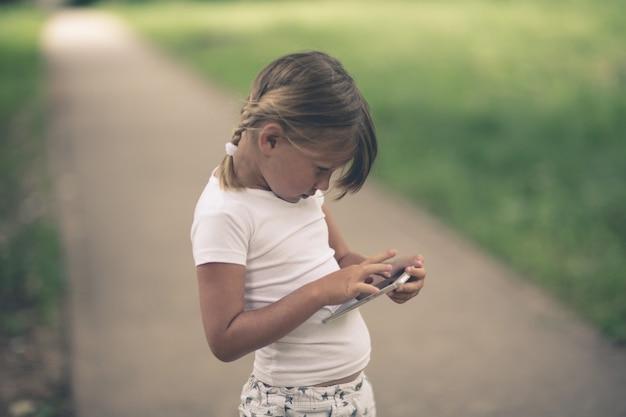 Gericht meisjeskind met smartphone, in openlucht,