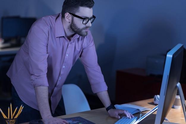 Gericht op werk. aantrekkelijke slimme bebaarde man op een knop te drukken en te kijken naar het computerscherm terwijl hij ervoor staat