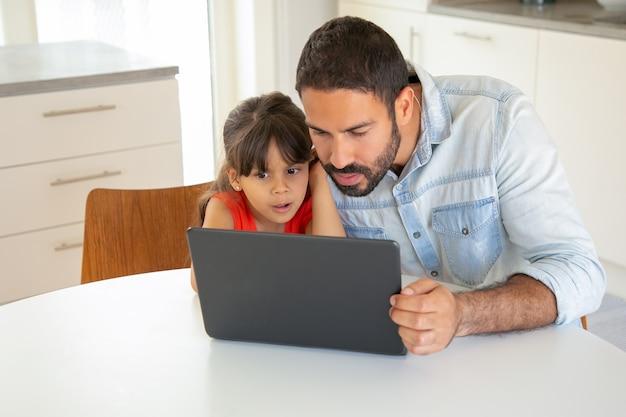 Gericht opgewonden meisje en haar vader met behulp van laptop, zittend aan tafel, display staren.