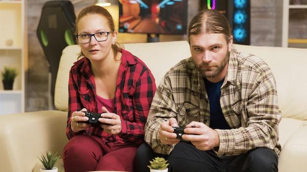 Gericht paar spelen online videogames zittend op de bank in de woonkamer. games spelen met draadloze controllers.