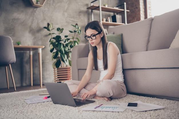 Gericht slimme deskundige meisje zit tapijt benen gekruist werk laptop