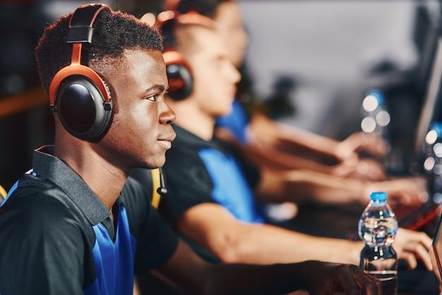 Gerichte afrikaanse mannelijke cybersport-gamer die een koptelefoon draagt die deelneemt aan esport-toernooien zittend