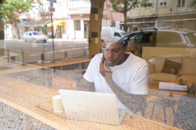 Gerichte afro-amerikaanse ondernemer die op laptop werkt en op mobiel in co-working space spreekt