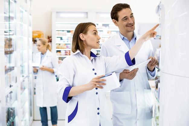 Gerichte apothekers staan voor een glazen kast in een apotheek met een tablet, controleren