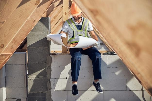 Gerichte architect die een blauwdruk controleert terwijl hij onder een houten dakkarkas zit