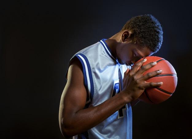 Gerichte basketbalspeler poseert met bal in studio, zwarte achtergrond. professionele mannelijke baller in sportkleding die sportspel speelt, lange sportman