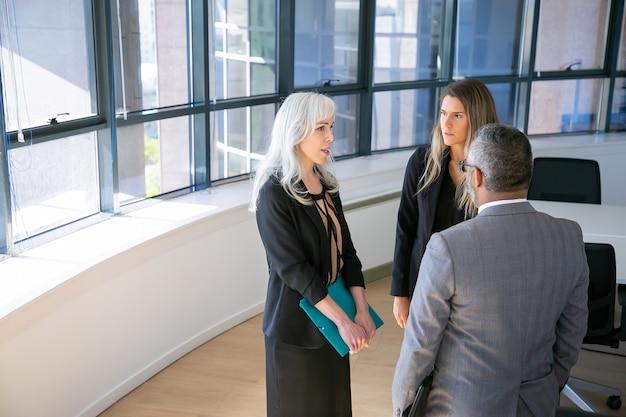 Gerichte bedrijfsgroep staan en praten in kantoor, praten, project- en werkkwesties bespreken. kopieer ruimte. zakelijke communicatie of briefing concept