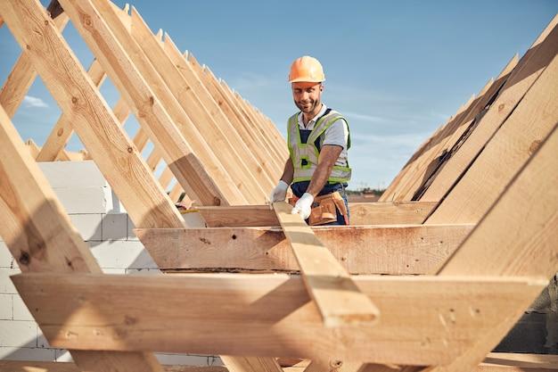 Gerichte bouwer die een veiligheidshelm draagt en een lang stuk hout vasthoudt voor het bouwen van een dakkarkas