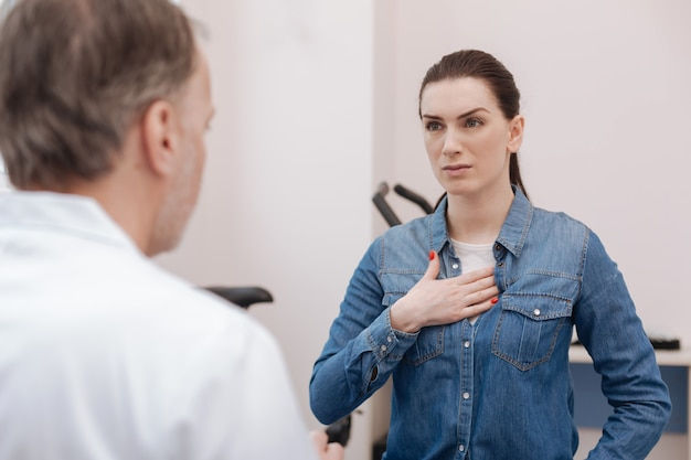 Gerichte emotionele prachtige dame die de dokter over haar zorgen vertelt en haar symptomen uitlegt terwijl ze bezorgd kijkt