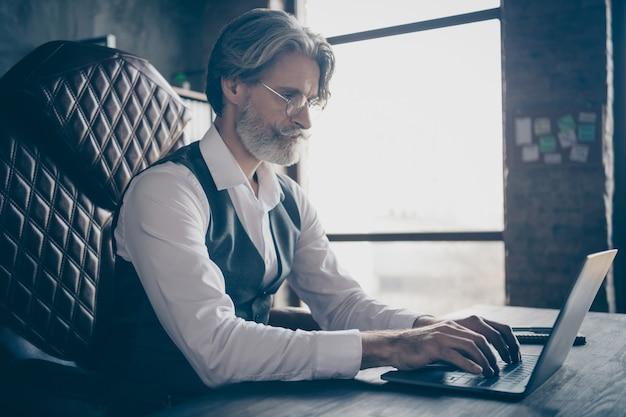 Gerichte ernstige zakenman typen op laptop in kantoor