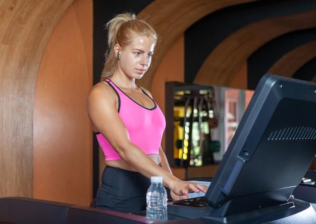 Gerichte fitte vrouw met loopband in sportschool