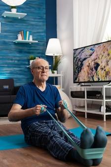 Gerichte gepensioneerde zittend op een yogamat die de spieren van de benen uitrekt met behulp van een elastische band van fitness tijdens aerobicstraining die de weerstand van de spieren uitoefent
