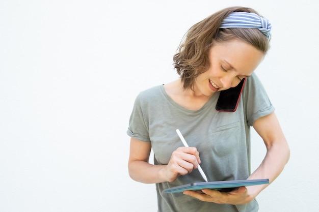 Gerichte glimlachende jonge vrouw die op het tabletscherm schrijven