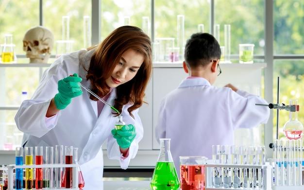 Gerichte jonge aziatische vrouwelijke chemicus in laboratoriumjas en handschoenen die kleurrijke chemische vloeistoffen in kolven mengen terwijl ze onderzoek doen in het laboratorium.