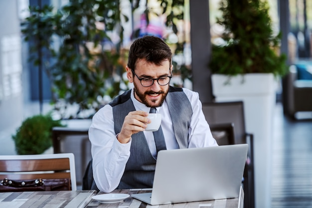 Gerichte kaukasische knappe bebaarde zakenman in pak en met bril kopje koffie te houden en laptop gebruikt. cafe buitenkant.