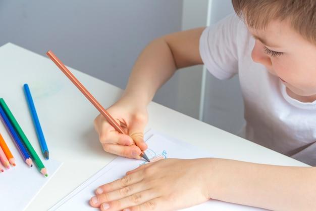 Gerichte kleuter kleine jongen 5-6 jaar tekent nauwgezet tekening met potlood