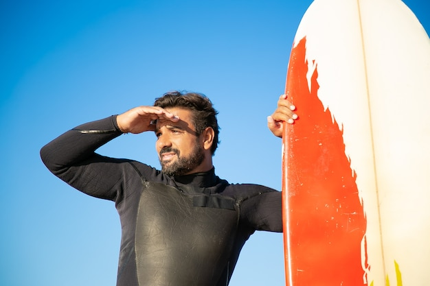 Gerichte knappe surfer die in de verte staart