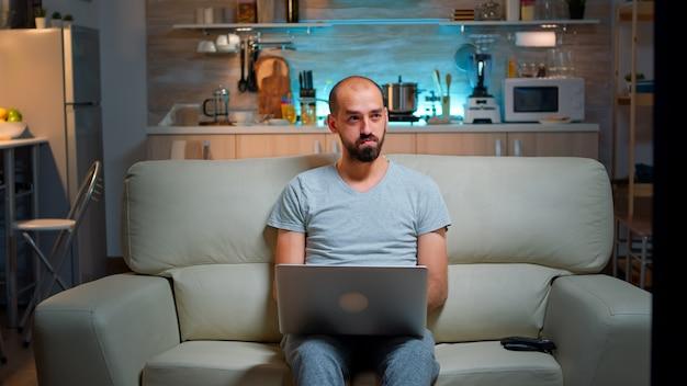 Gerichte man zittend op de bank en online project schrijven op laptop