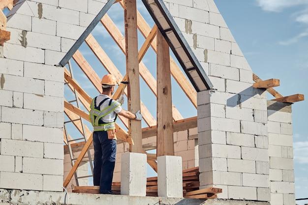 Gerichte mannelijke bouwer die veiligheidsuitrusting draagt terwijl hij bovenop het huis staat en een spijker in het hout steekt.
