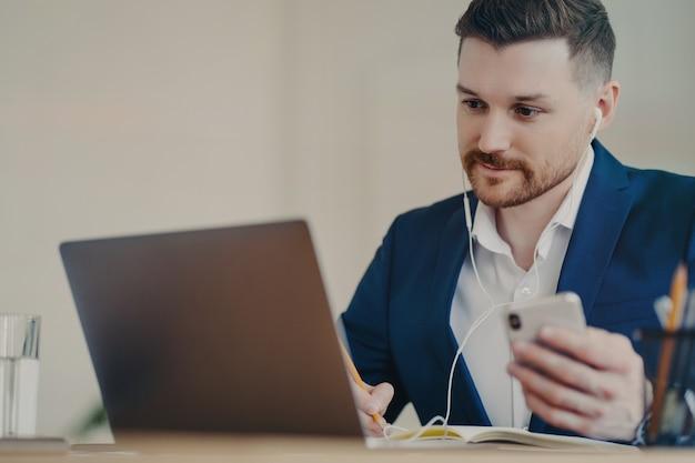 Gerichte mannelijke directeur die bedrijfskleding draagt in draadloze oortelefoons met mobiele telefoon in de hand, kijken naar zakelijke webinars op laptop of videobellen, werkend in een gezellige kast. baanbezettingsconcept