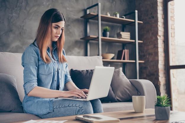 Gerichte marketeer uitvoerend meisje zit divan werk laptop thuis