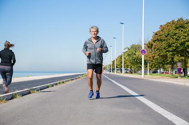 Gerichte moe volwassen man in sportkleding joggen langs de rivieroever buiten. senior jogger training voor marathon. vooraanzicht. activiteit en leeftijd concept