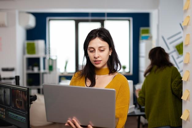 Gerichte ondernemer die in het kantoor van een creatief bureau staat en een laptop vasthoudt en projectinformatie typt