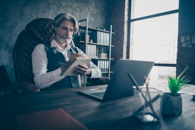 Gerichte oude man agent zitten mke-tafelnota in voorbeeldenboek op kantoor