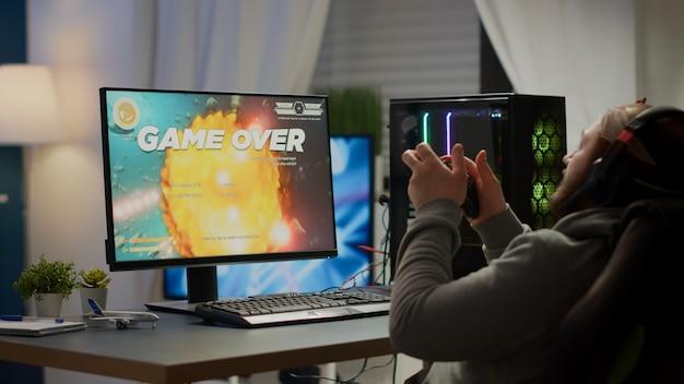 Gerichte pro cyber die de handen op het hoofd houdt na het verliezen van een space shooter-videogame met behulp van een draadloze joystick. boze gamer met professionele headset voor online esports-kampioenschap zittend op gamestoel