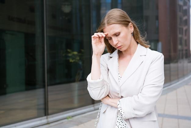 Gerichte professioneel denkende jonge blanke zakenvrouw in een licht jasje dat in de buurt van een kantoor staat...