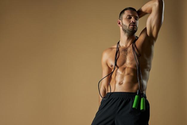 Gerichte schattige sportman in zwarte korte broek die wegkijkt met springtouw op zijn geïsoleerde schouder