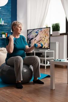 Gerichte senior man met halters werkende spieren oefenen streching lichaam training arm spierweerstand. pensioen kaukasisch mannetje zittend op de zwitserse bal in de woonkamer aan het doen van fitnesstraining