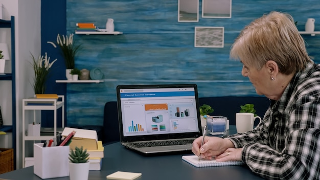Gerichte senior ondernemer die afbeeldingen van laptop controleert