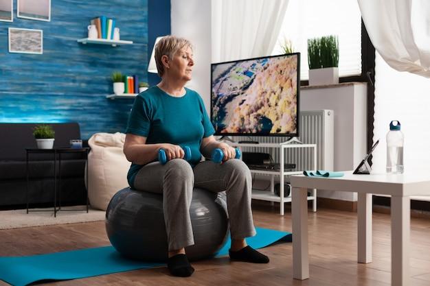 Gerichte senior vrouw die arm traint met behulp van workout-halters die op een zwitserse bal in de woonkamer zitten. gepensioneerde in sportkleding kijkt naar online aerobicstraining op tablet die lichaamsweerstand uitoefent