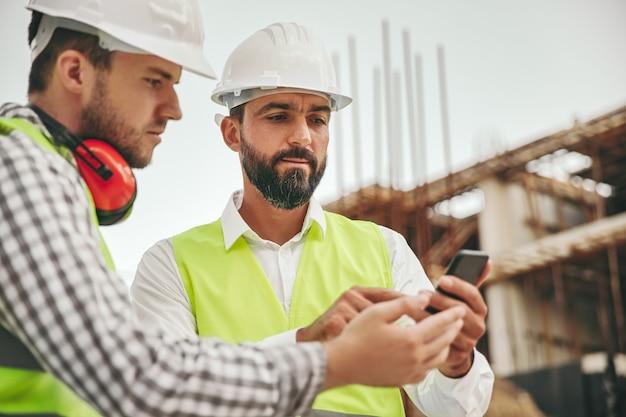 Gerichte serieuze diverse mannelijke architecten in hardhats met behulp van mobiele app op smartphone en details van project controleren terwijl ze samenwerken op de bouwplaats