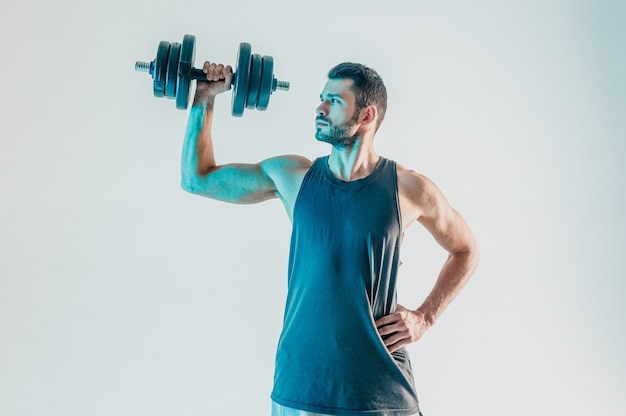 Gerichte sportman die schouderspieren traint met halter. jonge, bebaarde europese man draagt sportuniform. geïsoleerd op turkooizen achtergrond. studio opname. ruimte kopiëren